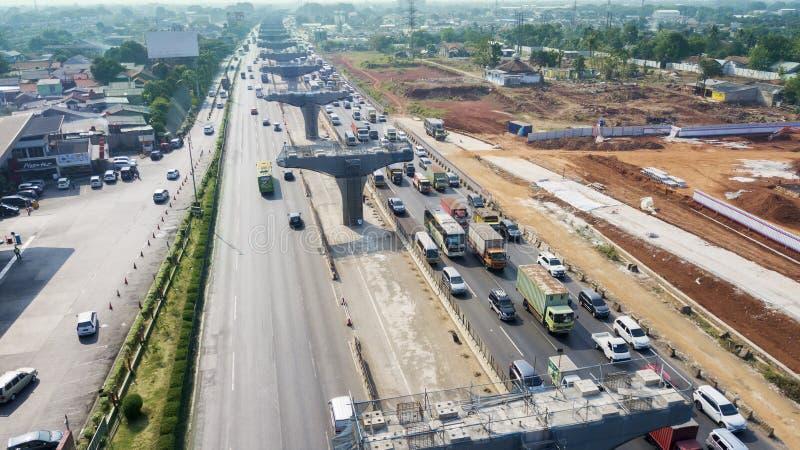 Construction pilings in Jakarta-Cikampek toll road. West Java, Indonesia - October 10, 2018: Aerial view of hectic traffic with construction pilings of the stock image