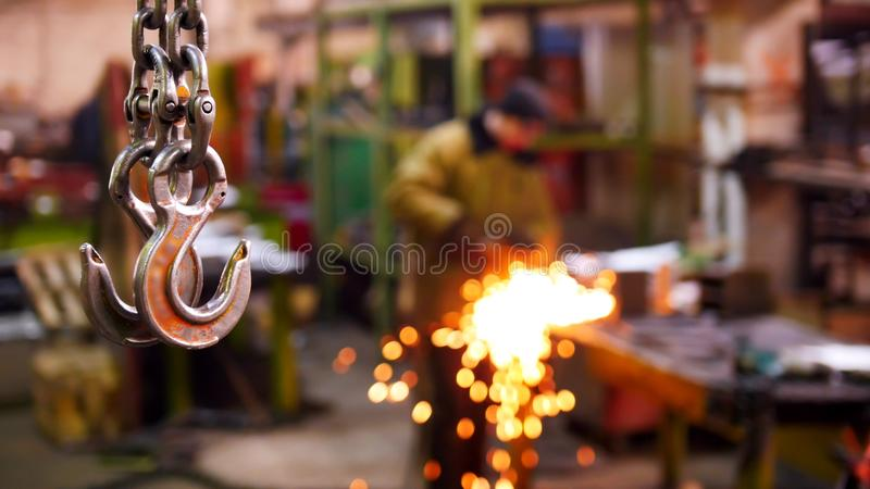 Construction plant. A big industrial lifting chain with a hook on the end hanging in the air. A man welding on the. Background. Mid shot stock photography