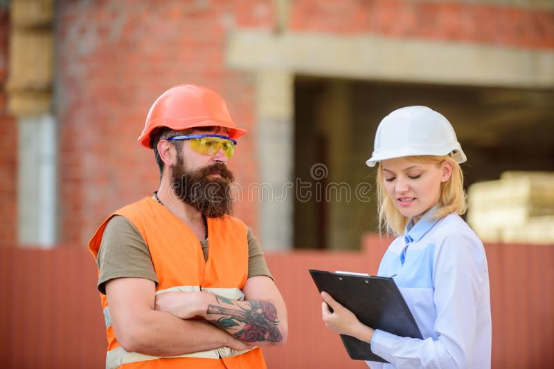 Construction project inspecting. Construction site safety inspection. Discuss progress project. Safety inspector concept royalty free stock images