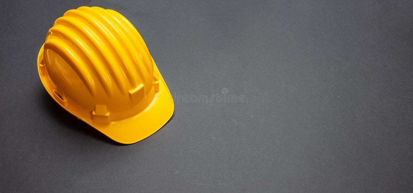 Construction project safety, Yellow hard hat on black color background. Copy space royalty free stock image