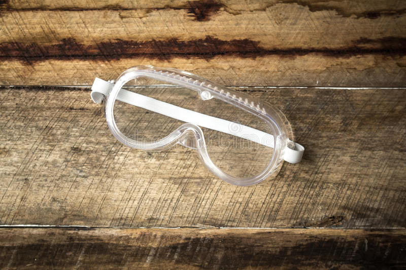 Construction protective eye wear. Construction background with protective eye wear on rustic floor boards stock image