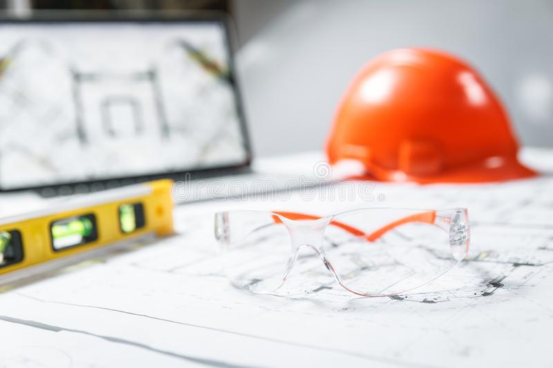 Construction protective glasses,orange hard hat, laptop  with drawings, level meter lying in a  blueprints on a table stock photo