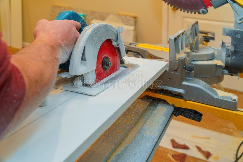Construction remodeling home cutting wooden trim board on with hand circular saw. Cutting wooden trim board on with hand circular saw works on remodeling home royalty free stock images