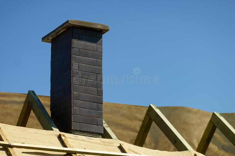 Construction of the roof. Construction of a clinker brick chimney. Construction of roof. Construction of a clinker brick chimney royalty free stock photography