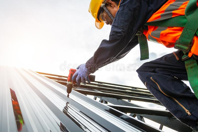 [Construction roof] Roofer worker in protective uniform wear and gloves, Construction worker install new roof,Roofing tools, stock photo