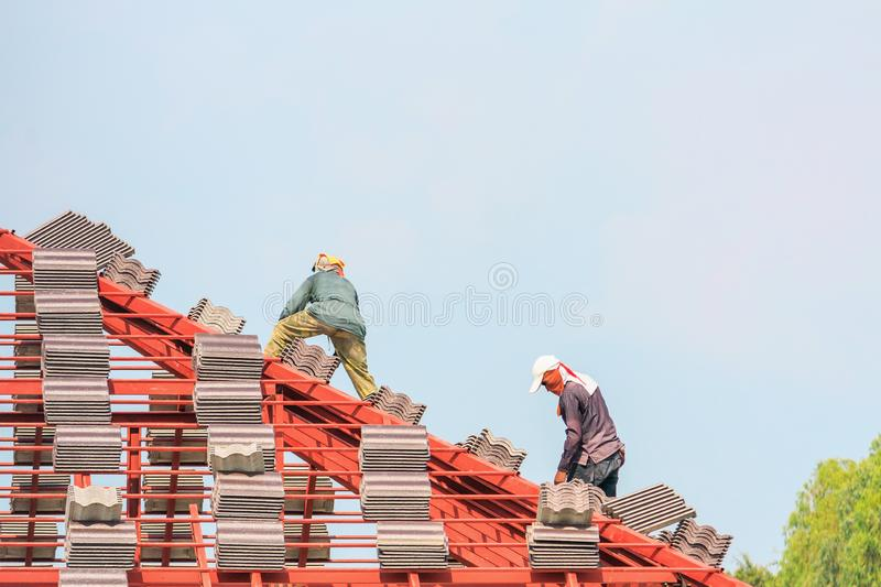 Construction roofer installing roof tiles at house building site royalty free stock photo