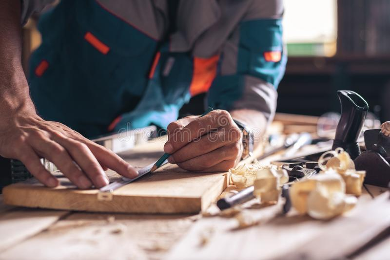 Construction, roofing, woodworking. Close-up of the hands of a carpenter, a worker with a pencil makes a mark on a wooden board royalty free stock images
