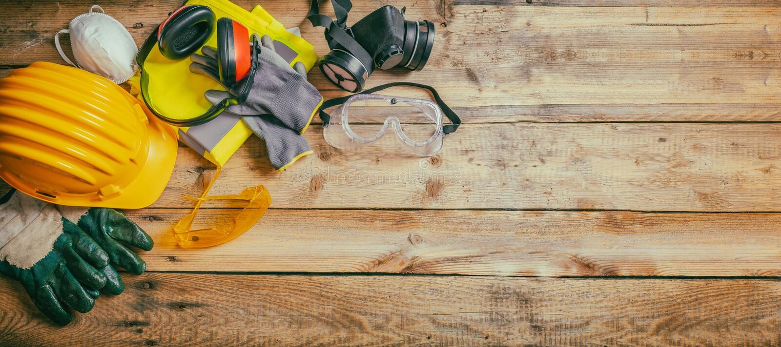 Construction safety. Protective hard hat, headphones, gloves and glasses on wooden background, banner stock photo