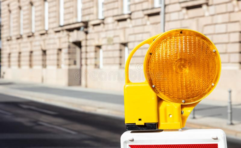 Construction safety. Street barricade with warning signal lamp on a road, blur building background. Construction site and safety. Street barricade with warning royalty free stock image