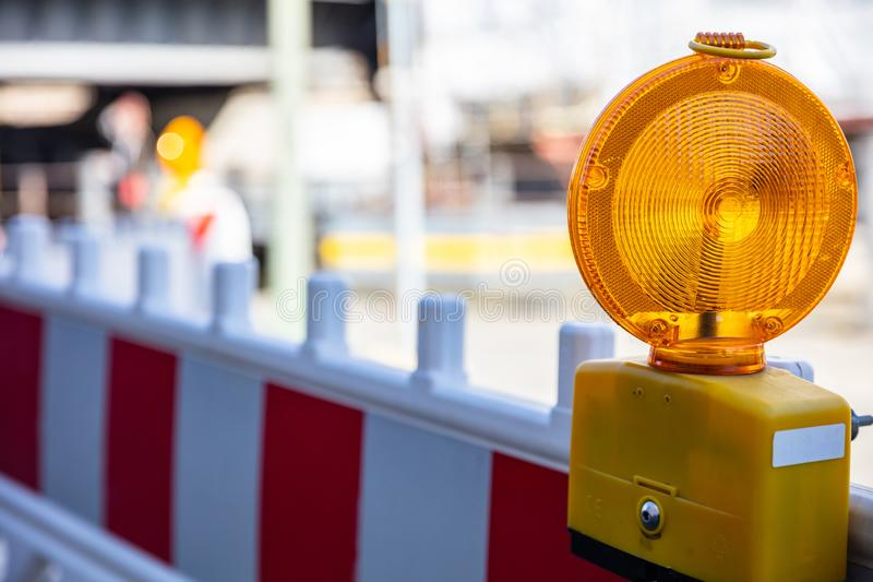 Construction safety. Street barricade with warning signal lamp on a road, blur site background. Construction site and safety. Street barricade with warning royalty free stock image