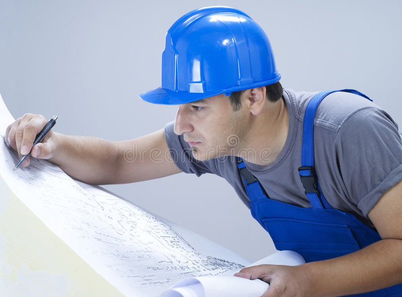 Construction series. Construction engineer working on blueprints royalty free stock images