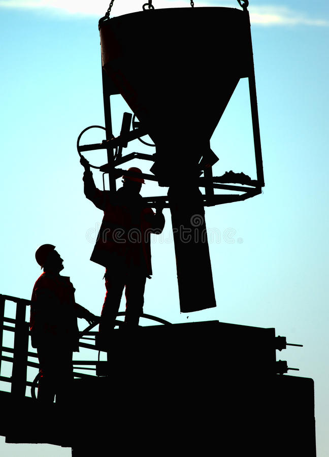 Construction site. Two builders pouring cement at construction site royalty free stock photography