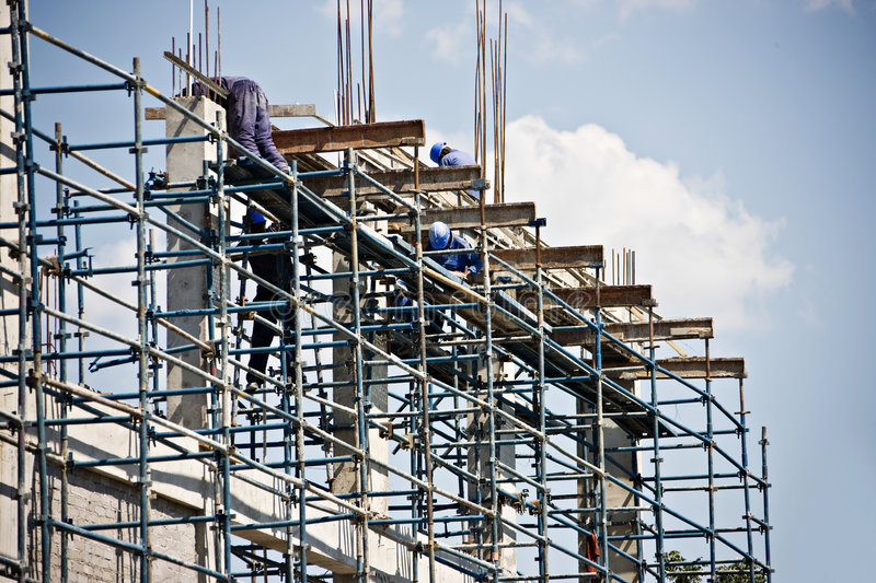Construction site. Construction workers climbed on scaffolding royalty free stock photography