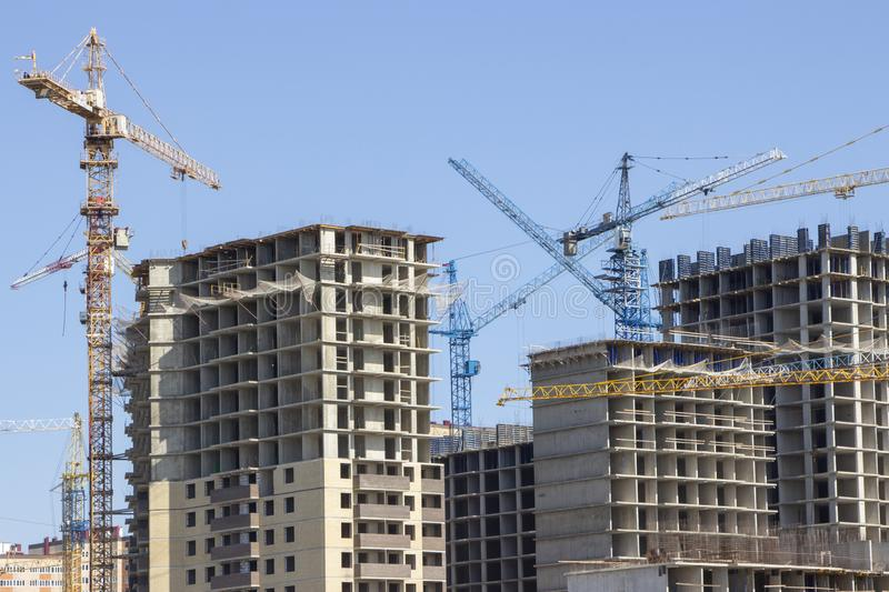 Construction site background. Hoisting cranes and new multi-storey buildings. tower crane and unfinished high-rise building. many stock photo