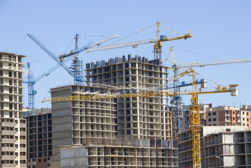 Construction site background. Hoisting cranes and new multi-storey buildings. tower crane and unfinished high-rise building. many royalty free stock photo