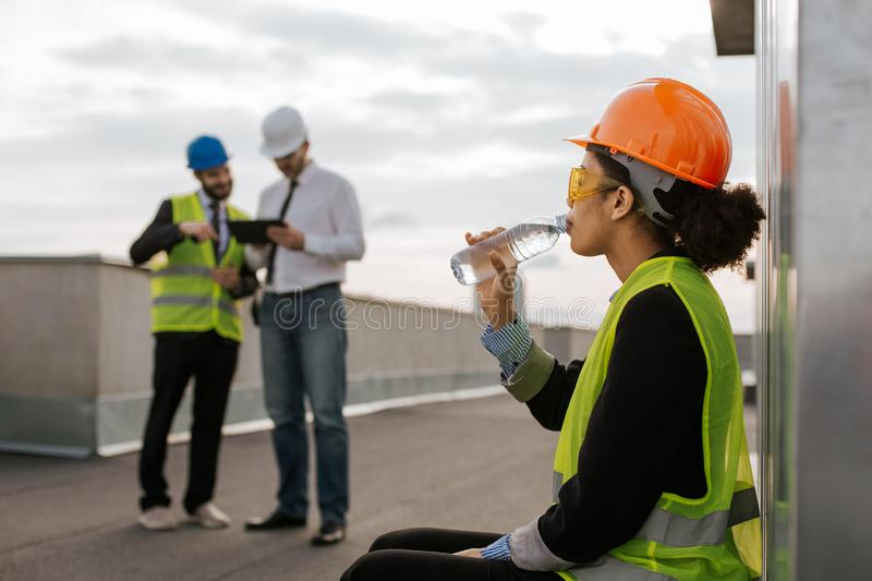 On construction site beautiful smiling African lady engineer drinking some water from bottle on the rooftop of building royalty free stock photography