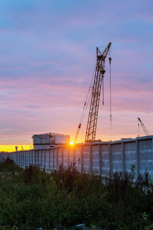 Construction site behind a concrete fence. At sunset stock photography