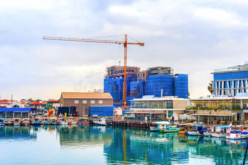 Construction site, boats, waterfront, Cyprus. Construction site by Limassol waterfront, boats moored in marina with cafes and restaurants, Cyprus royalty free stock images