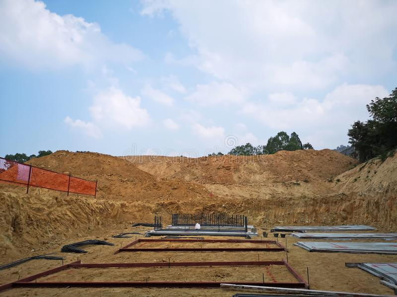 Construction site, brown land at infrastructure on ground area under beautiful white fluffy clouds and vivid blue sky in a suny. Day royalty free stock image