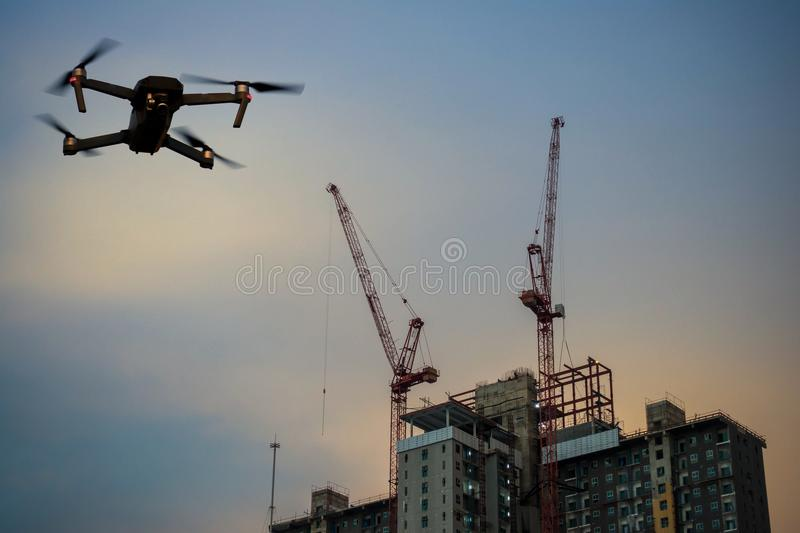 Construction site building with crane and drone. Modern RC Drone / Quadcopter with camera flying on Construction site with crane. double exposure stock photos
