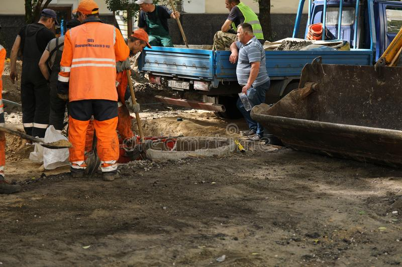 Kyiv/Ukraine - 18 may 2019:Construction site with communal service workers in orange uniform and construction machinery royalty free stock image