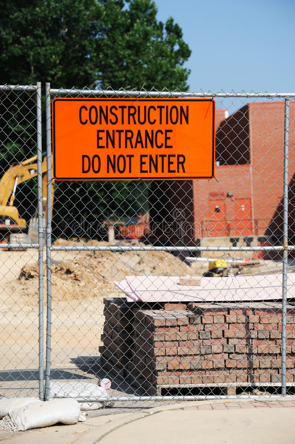Construction site with construction material, iron fence and warning message board stock photography