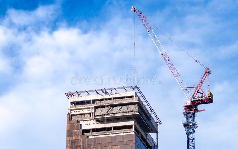 Construction site with crane and building. Real estate industry. Crane use reel lift up equipment in construction site. Building. Made of steel and concrete royalty free stock photography