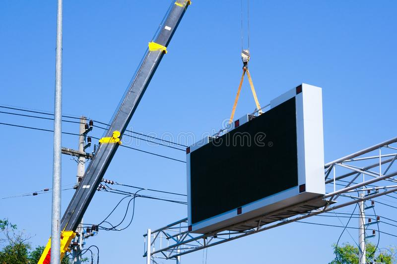 Construction site crane is lifting a led signboard Blank billboard on blue sky background for new advertisement stock photos