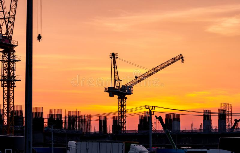 Construction site with crane and sunset sky. Real estate industry. Crane use reel lift up equipment in construction site. Building stock photography