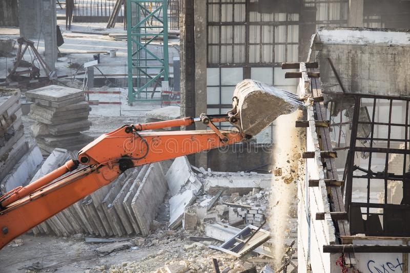 Excavator bucket destroys an old building on site royalty free stock images