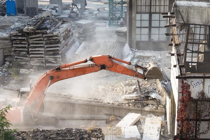 Excavator bucket destroys an old building on site royalty free stock image