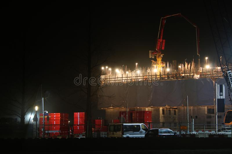 Construction site with a group of construction workers that are working on a building during the night stock images