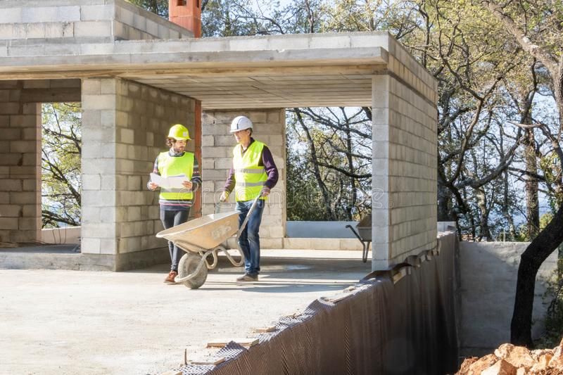 Building engineer and mason during a construction site visit, construction of a house. Construction site house, construction site visit, construction industry royalty free stock images
