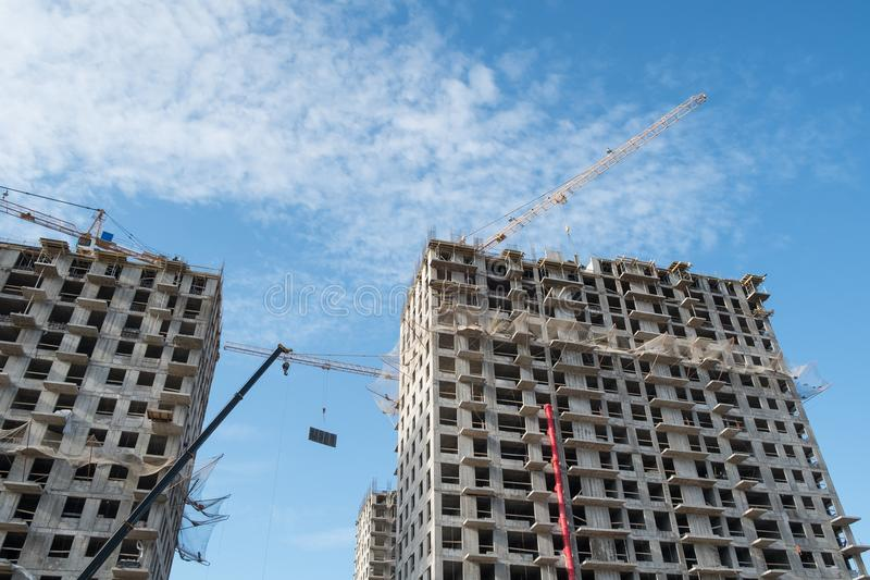 Construction site on blue sky. Construction site with a lot of incomplete buildings with cranes. Work in progress. New home in future stock photo