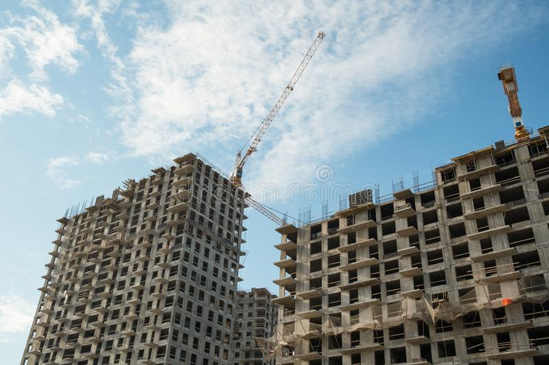 Construction site on blue sky. Construction site with a lot of incomplete buildings with cranes. Work in progress. New home in future royalty free stock photos