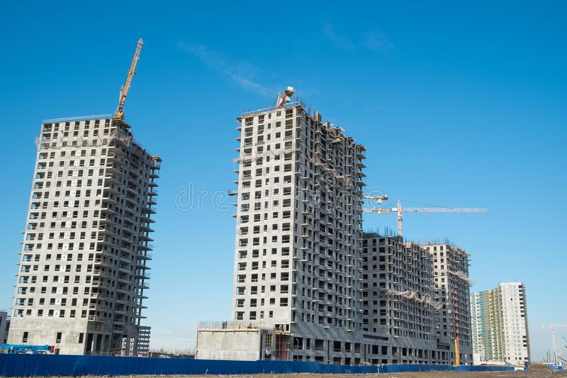 Construction site on blue sky. Construction site with a lot of incomplete buildings with cranes. Work in progress. New home in future royalty free stock images