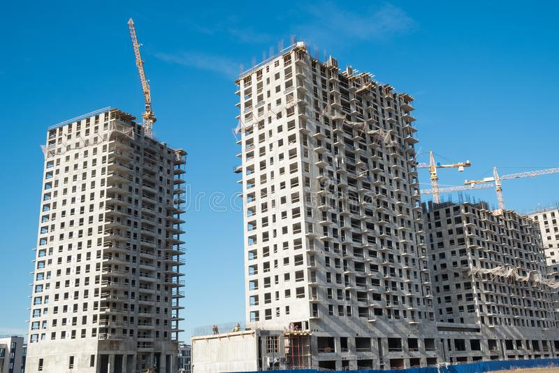 Construction site on blue sky. Construction site with a lot of incomplete buildings with cranes. Work in progress. New home in future royalty free stock image