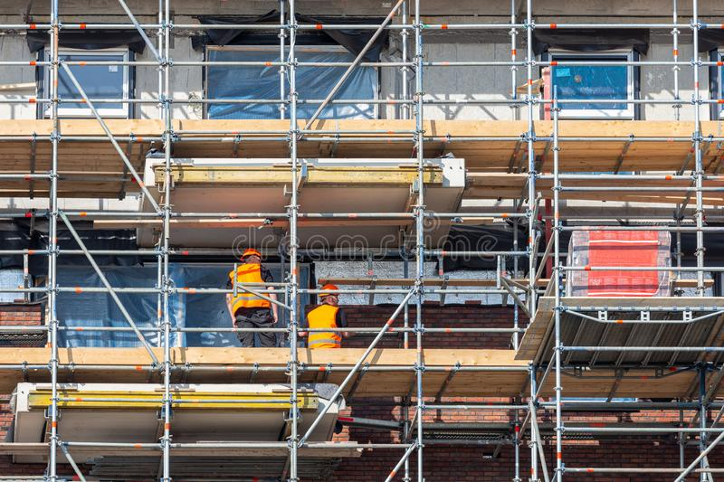Construction site new apartment building with scaffolding and mason workers stock image