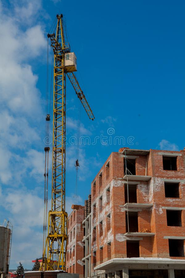 Construction site of a new apartment high building with tower cranes against blue sky. Residential area development. Real estate p stock photography