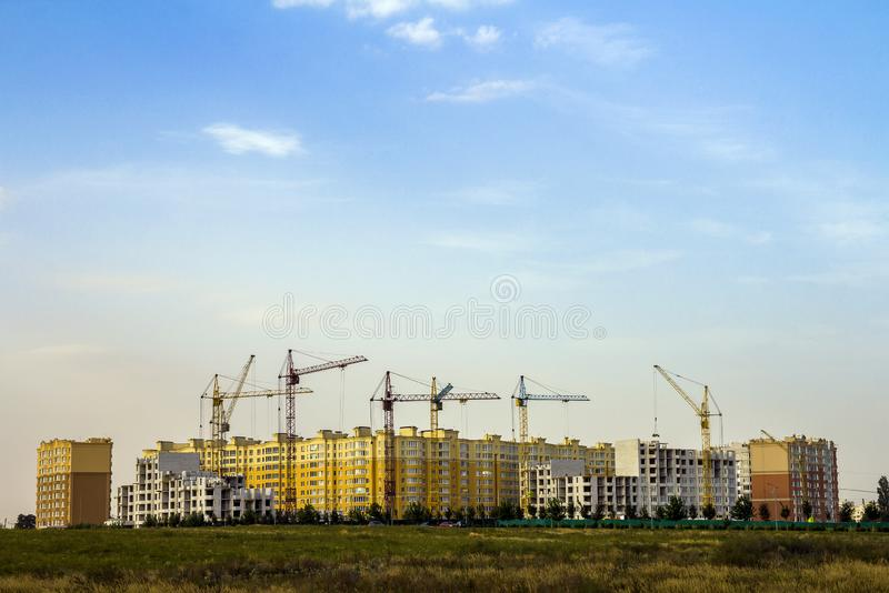 Construction site of a new apartment high building with tower cranes against blue sky. Residential area development. Real estate. Project growth concept stock image
