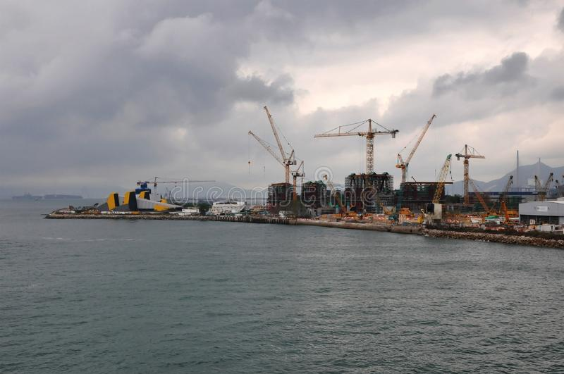 Construction Site of a new area of Hong Kong harbor with many cranes. And a very cloudy sky royalty free stock photos