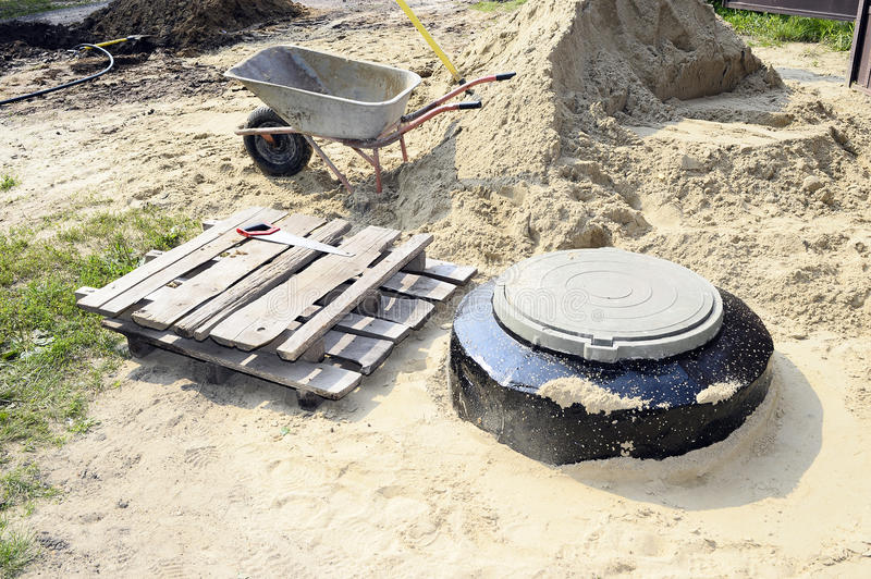 Construction site with new armed manholes, cart, sand and equipment.  stock photography
