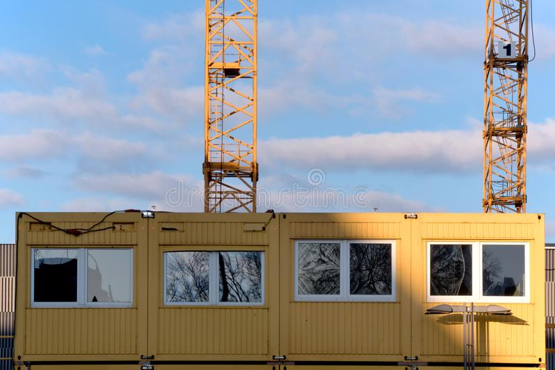 Construction site office and bottom of two yellow cranes against royalty free stock image