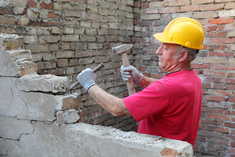 Construction site, old building demolishing. Construction worker demolishing old brick wall with chisel tool and hammer royalty free stock image