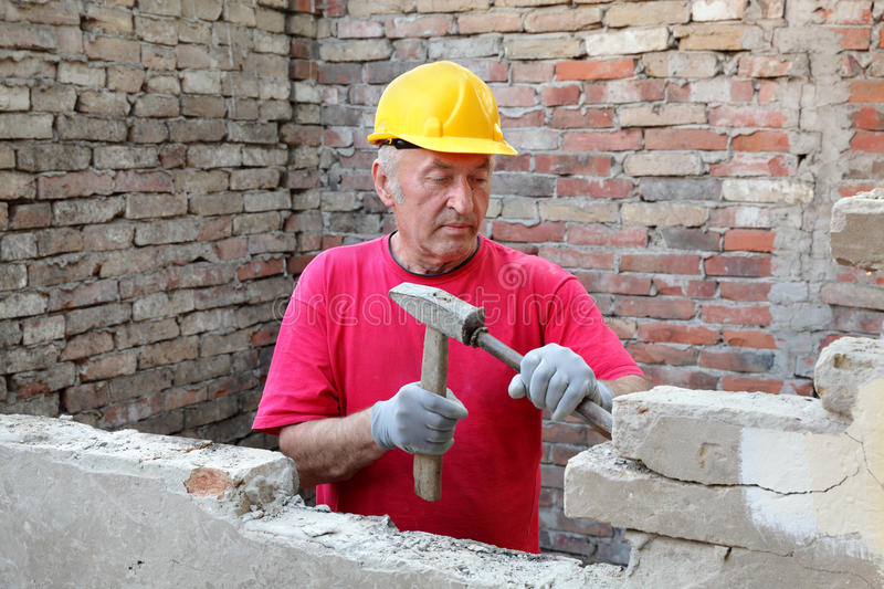 Construction site, old building demolishing. Construction worker demolishing old brick wall with chisel tool and hammer, real people royalty free stock images