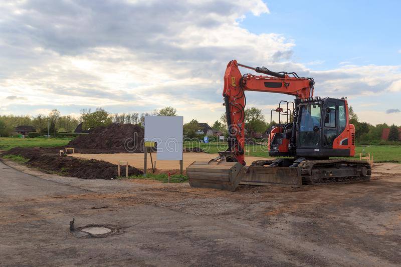 Construction site for one family house filled with sand, empty sign with copy space and digger in building area after earthworks, royalty free stock photos