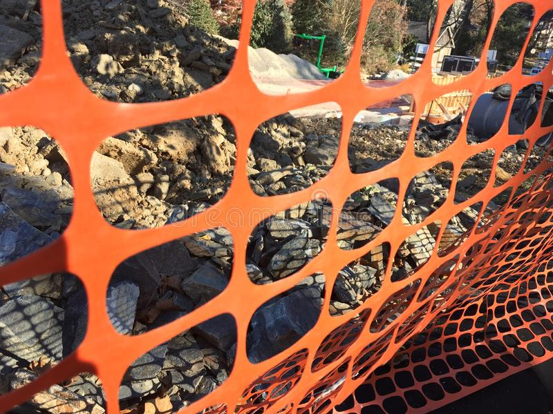 Construction site orange fence. Orange fence on a construction site with debris, road work infrastructure royalty free stock photos