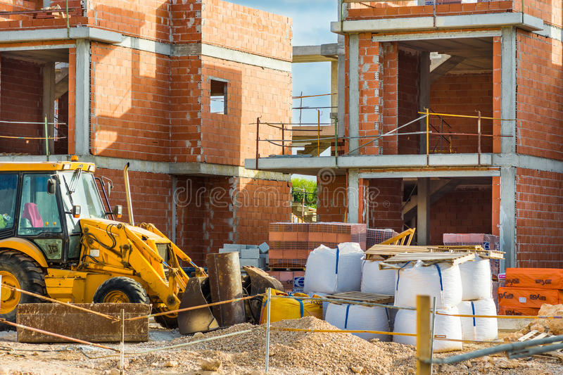 Construction site red brick residential townhouses, concrete pillars, digger, piles of materials, unfinished new build. Sunlight, mediterranean stock image