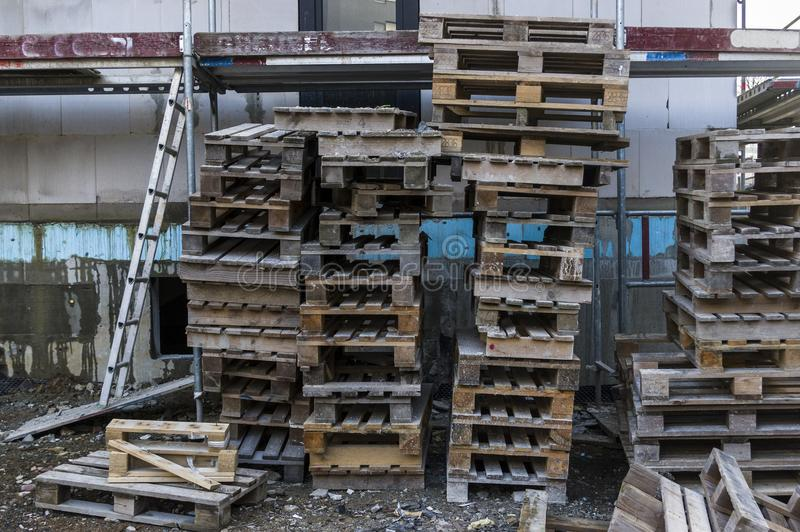 Construction site Residential building with scaffolding for facade insulation with several stacks of wooden pallets stock photos