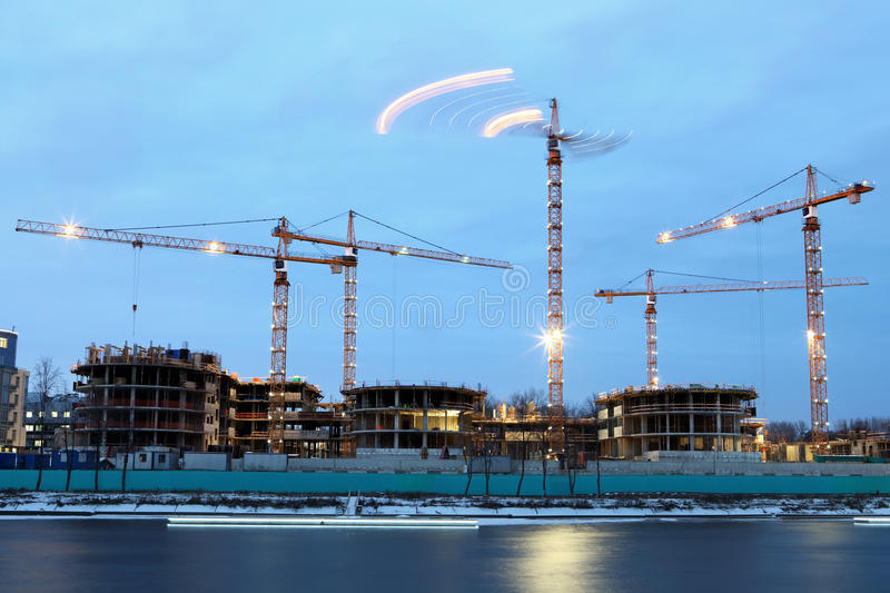Construction site of residential building, tower cranes with ev. Construction machinery on the construction of residential buildings, night time Evening royalty free stock image
